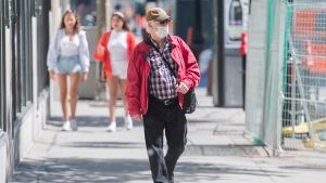 A man wears a face mask as he walks along a street in Montreal, Sunday, June 14, 2020, as the COVID-19 pandemic continues in Canada and around the world. THE CANADIAN PRESS/Graham Hughes