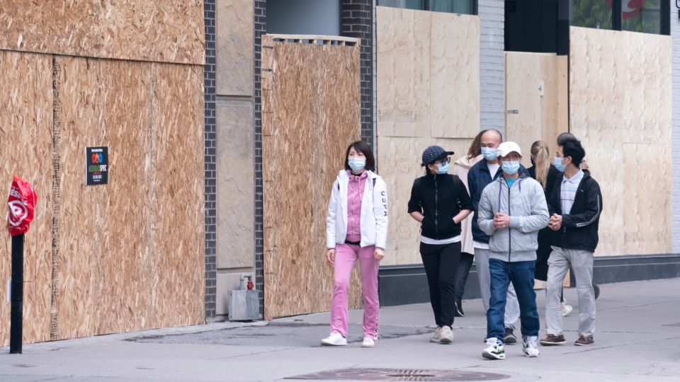 Shoppers walk past boarded up stores on Montreal's Sainte-Catherine street on Wednesday, June 3, 2020. (THE CANADIAN PRESS / Paul Chiasson)