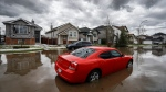 A hail damaged car parked on a flooded street as residents begin cleaning up in Calgary, Alta., Sunday, June 14, 2020, after a major hail storm damaged homes and flooded streets on Saturday.THE CANADIAN PRESS/Jeff McIntosh