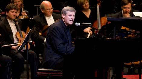 Prime Minister Stephen Harper, centre, sings as he plays The Beatles song 'With a Little Help From My Friends' at the National Arts Centre Gala in Ottawa, Ont., Saturday Oct. 3, 2009. (Sean Kilpatrick / THE CANADIAN PRESS)