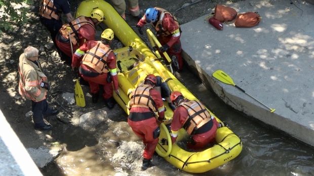 Emergency crews work at the scene where a woman fell down an embankment in London, Ont. on Monday, June 15, 2020. (Jim Knight / CTV London)