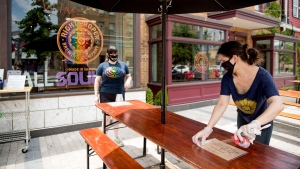 Owner Leah Cheston, right, and Assistant General Manager Tylyn Mallon, left, set up the outdoor patio at Right Proper Brewing Company in the Shaw neighborhood in Washington, Friday, May 29, 2020, after the District of Columbia gradually loosens stay-at-home rules that have been in place since March 25 because of the pandemic and allows restaurants to resume outdoor dining. (AP Photo/Andrew Harnik)