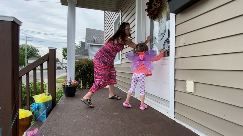 Victoria Lappe and daughter Mackenzee performing a Ding-Dong-Ditch gift drop. June 10, 2020. Hawkesbury, ON. (Tyler Fleming / CTV News)
