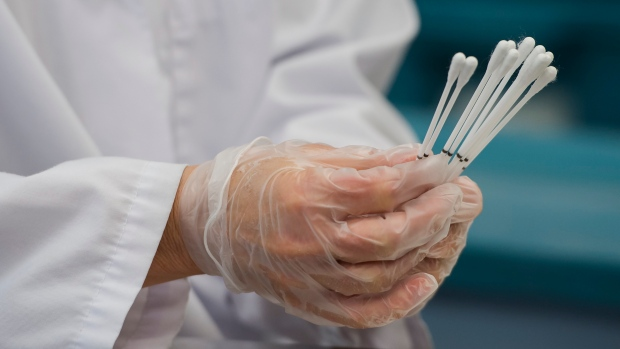 Employees work at the Canadian Hospital Specialities (CHS) helping take dual COVID-19 testing swab kits and separating them into two units to help with swab capacity during the COVID-19 pandemic in Oakville, Ont., on Monday, June 8, 2020. THE CANADIAN PRESS/Nathan Denette