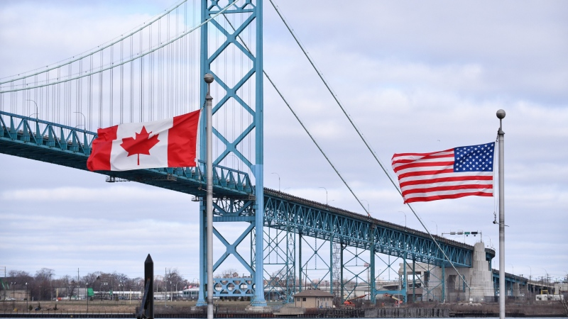 Canadian and American flags fly near the Ambassador Bridge at the Canada-USA border crossing in Windsor, Ont. on Saturday, March 21, 2020. THE CANADIAN PRESS/Rob Gurdebeke