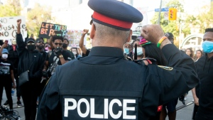 A police officer throws up a fist as protesters march in an anti-racism rally in Toronto, on Saturday, June 6, 2020. THE CANADIAN PRESS/Chris Young