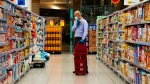 In this April 19, 2020 photo, a customer at a Carrefour supermarket wearing a face mask amid the coronavirus pandemic shops in the store in Dubai, United Arab Emirates. (AP / Jon Gambrell)
