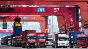Trucks line up to transport containers at the container port in Qingdao in eastern China's Shandong province, on June 2, 2020.(Chinatopix via AP)