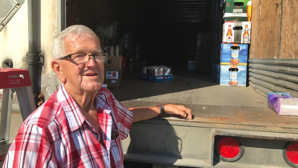 Wayne Kinney, a member of the Royal Canadian Legion Victory Branch, stands at the rear of a transport donated for a bottle drive in London, Ont. on Thursday, June 18, 2020. (Sean Irvine / CTV News)