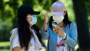 People wearing masks use their smart phones during the COVID-19 pandemic in Toronto on Thursday, June 18, 2020. The Government of Canada along with provinces have announced a new downloadable contact tracing app for COVID-19, which is optional for people to use. THE CANADIAN PRESS/Nathan Denette