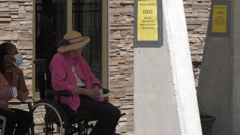 Long term care home resident and staff member sit outside. Jun 18/20 (Ian Campbell/CTV Northern Ontario)