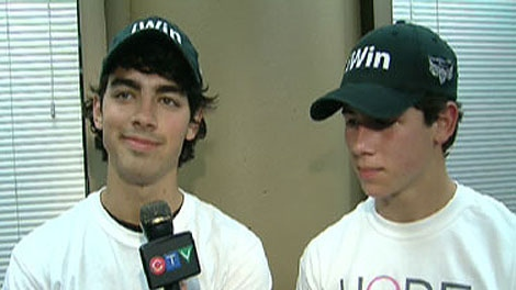Joe Jonas (left) and Nick Jonas do an interview after completing the Run for the cure in support of breast cancer research in Toronto on October 4, 2009.