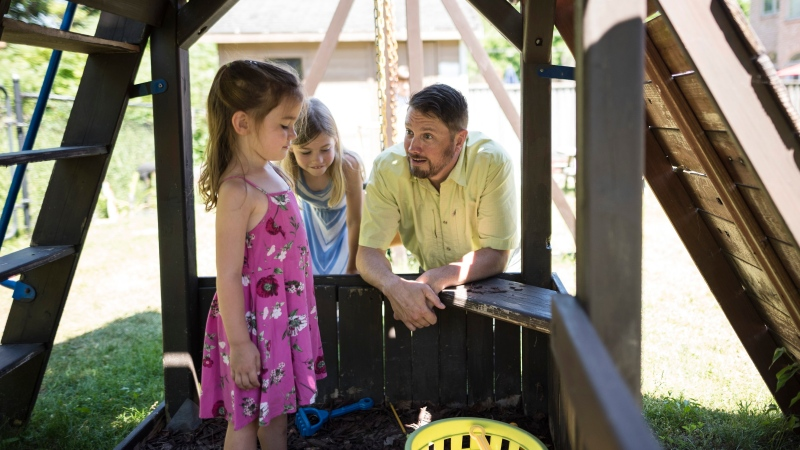 Joel Carty spends time in the backyard playhouse with his children Piper, 3, and Quinn, 7, at their home in Pickering, Ont., on Friday, June 19, 2020. THE CANADIAN PRESS/ Tijana Martin