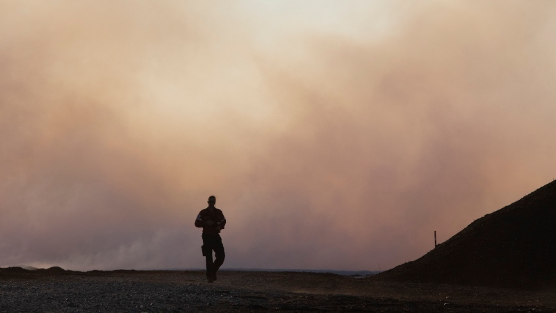 A firefighter walks toward a major field and forest fire at Lambert Peat moss fields in Riviere-Ouelle, Que., Friday, June 19, 2020. The fire spread over more than 10 km, pushed by strong winds. THE CANADIAN PRESS/Jacques Boissinot