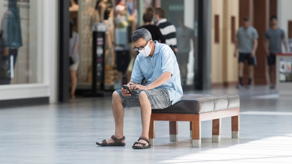 A man sits inside an open shopping mall in Montreal, Saturday, June 20, 2020, as the COVID-19 pandemic continues in Canada and around the world. THE CANADIAN PRESS/Graham Hughes