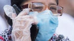 A woman wears a face mask and latex gloves as she talks on her phone in Montreal, Saturday, June 6, 2020, as the COVID-19 pandemic continues in Canada and around the world. (THE CANADIAN PRESS / Graham Hughes)
