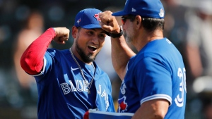 Toronto Blue Jays' Norberto Obeso, left, elbow bumps bench coach Dave Hudgens after the team's 7-5 win over the Pittsburgh Pirates in a spring training baseball game, Thursday, March 12, 2020, in Bradenton, Fla. (AP Photo/Carlos Osorio)