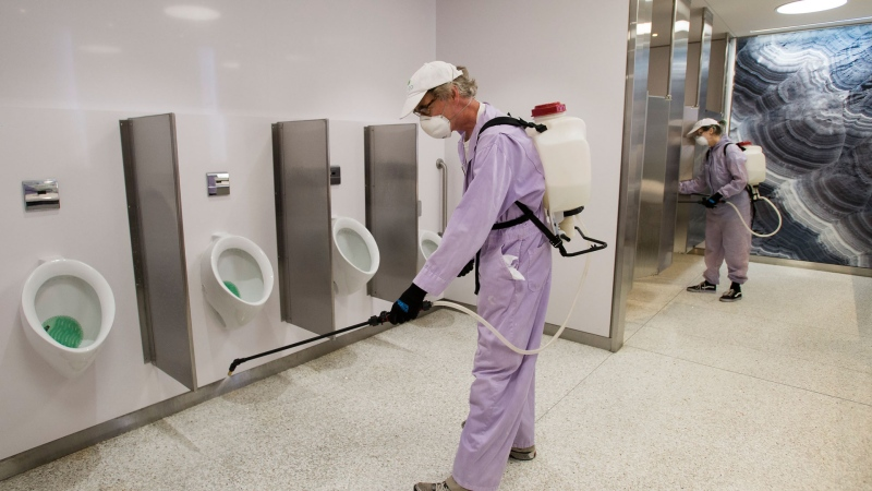 "Workers at Toronto's Pearson International Airport sprays down the men's washroom with probiotics for a ""Healthy Airport"" during the COVID-19 pandemic in Toronto on Tuesday, June 23, 2020. THE CANADIAN PRESS/Nathan Denette"