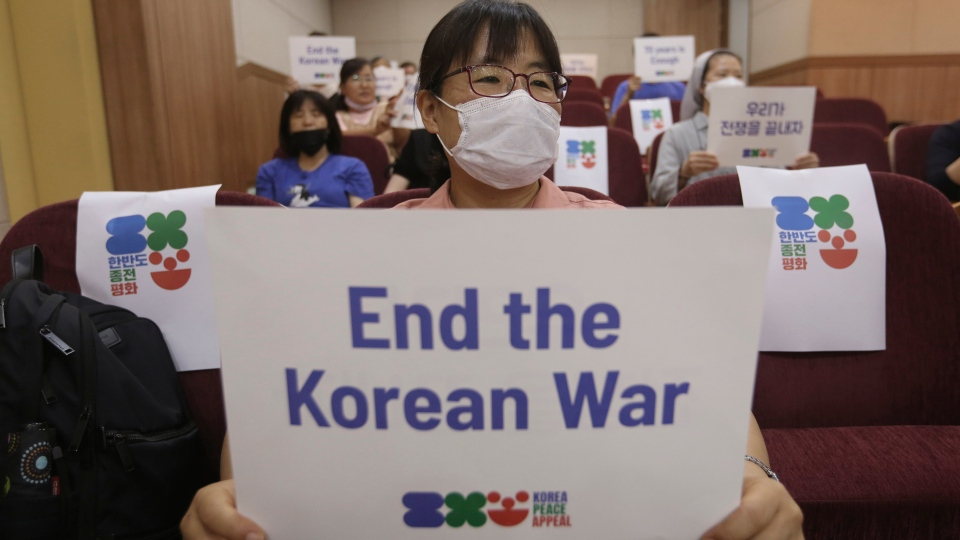 An anti-war activist holds a card during a press conference to demand the peace on the Korean peninsula on the eve of the 70th anniversary of the outbreak of the Korean War in Seoul, South Korea, Wednesday, June 24, 2020. (AP Photo/Ahn Young-joon)