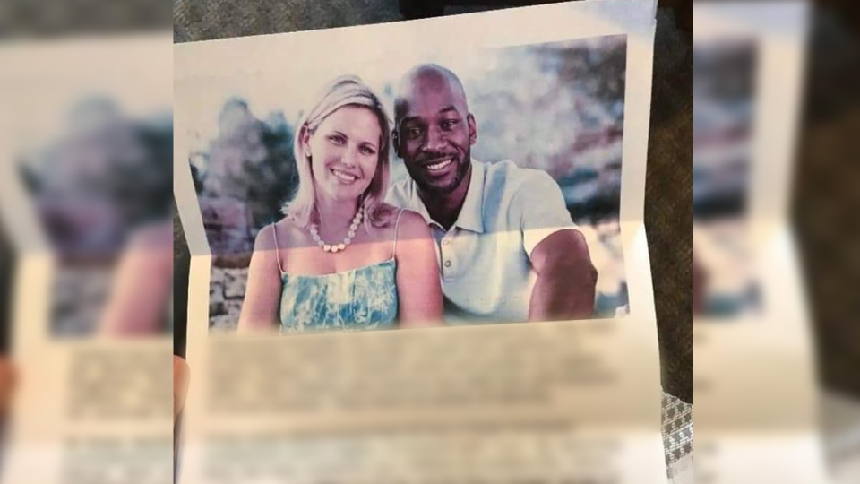 A photo of an interracial couple with blurred text