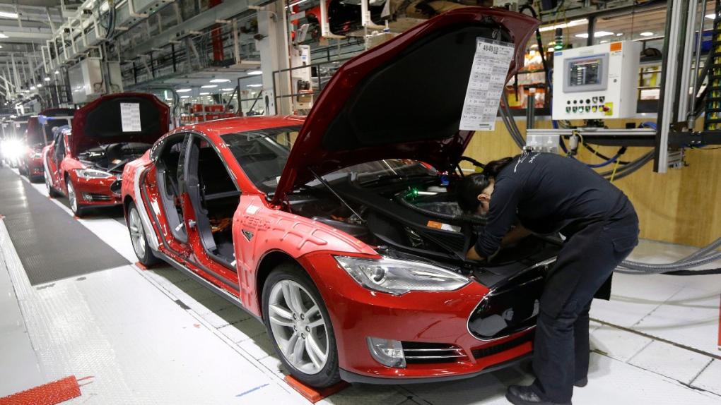 Tesla employees work on Model S cars