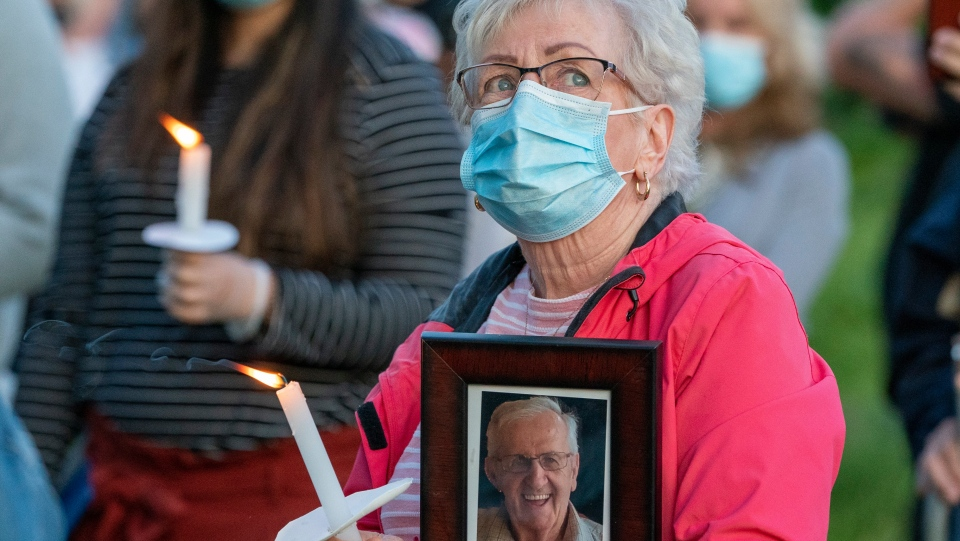 Participants react during a vigil for COVID-19 victims at the Orchard Villa long-term care home in Pickering, Ont. on Monday, June 15, 2020. THE CANADIAN PRESS/Frank Gunn