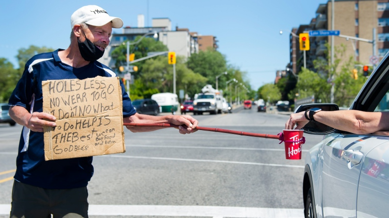 Raymond Martin uses a self-made contraption to properly physical distance while panhandling for money during the COVID-19 pandemic in Toronto on Tuesday, June 16, 2020. THE CANADIAN PRESS/Nathan Denette