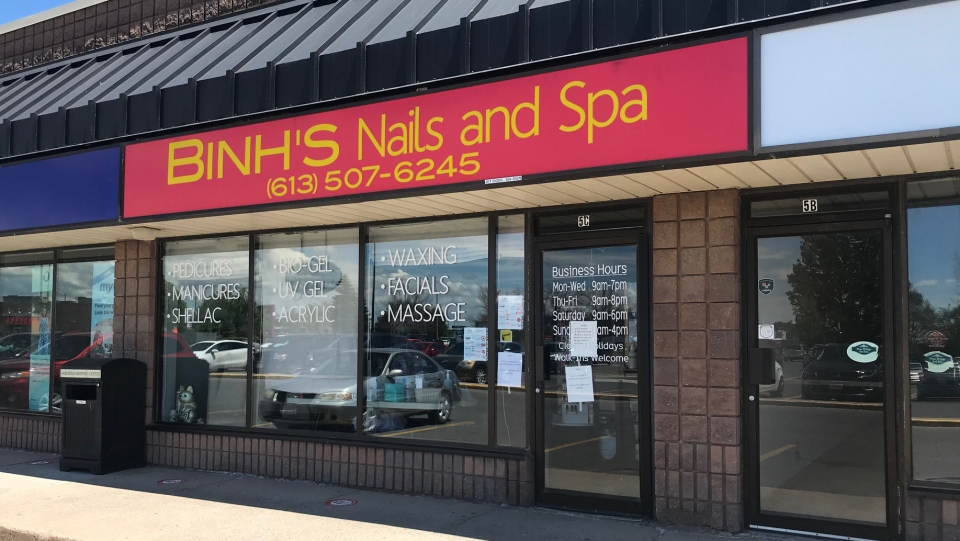 A sign on the door of Binh's Nails and Spa in Kingston says a customer tested positive for COVID-19. (Kimberley Johnson/CTV News Ottawa)