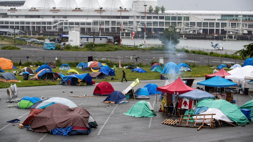 A man walks through a homeless camp where approximately 150 people are living at a parking lot on Port of Vancouver property adjacent to Crab Park, in Vancouver on June 10, 2020.. THE CANADIAN PRESS/Darryl Dyck