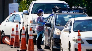 A healthcare worker interacts with motorists at a drive-thru COVID-19 testing facility Wednesday, June 17, 2020, in Dallas. The COVID-19 testing center in South Dallas is a partnership between the City of Dallas, Dallas County, CitySquare and Kroger Health. (Smiley N. Pool/The Dallas Morning News via AP)
