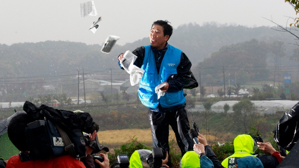 In this Oct. 22, 2012, file photo, Park Sang-hak, a North Korean refugee who launched balloons carrying propaganda balloons toward North Korea for years, hurls anti-North Korea leaflets as police block his planned rally on a road in Paju near demilitarized zone, South Korea. (AP Photo/Ahn Young-joon, File)