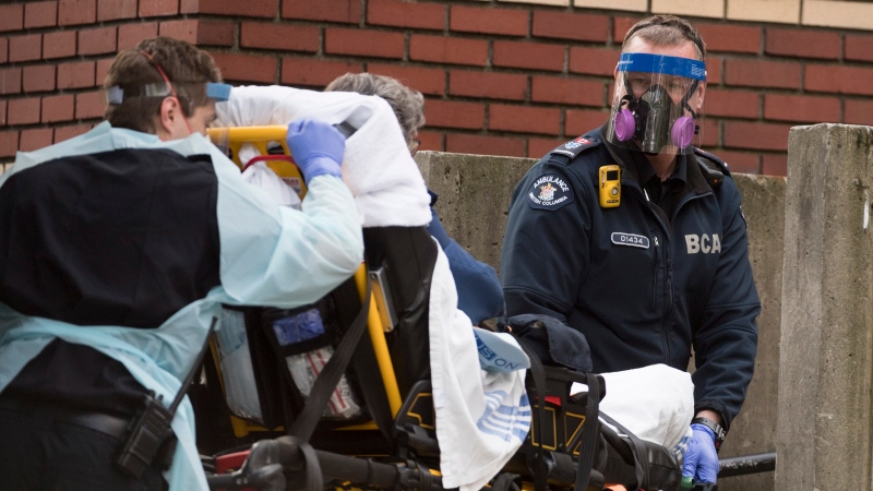 Members of the B.C. Ambulance Service wear protective face masks and shields as they transfer a patient to St. Paul's hospital in Vancouver, Monday, May 4, 2020. THE CANADIAN PRESS/Jonathan Hayward