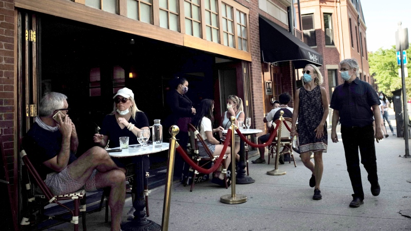 Passers-by, right, walk past diners at a cafe, Thursday, June 25, 2020, in Boston. (AP Photo/Steven Senne)