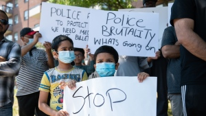 Children hold signs in front of the apartment building where Ejaz Choudry, a 62-year-old man who family members said was experiencing a schizophrenic episode, was shot by Peel Police and died at the scene the previous night, in Mississauga, Ont., Sunday, June 21, 2020. THE CANADIAN PRESS/Galit Rodan