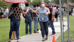In this Sunday, June 7, 2020, photo, Gretel Cacerces, right, passes out bottled water to those standing in line for COVID-19 testing at the Florida Department of Health in Collier County amid the new coronavirus pandemic in Immokalee, Fla. (AP Photo/Lynne Sladky)