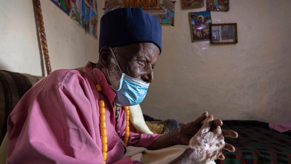 Centenarian Tilahun Woldemichael cries as he prays to God after spending weeks in hospital recovering from the coronavirus, at his house in Addis Ababa, Ethiopia Saturday, June 27, 2020. (AP Photo/Mulugeta Ayene)