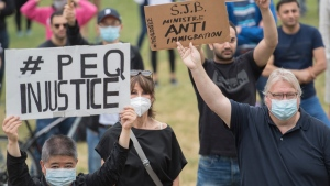 Former Quebec health minister Gaetan Barrette, right, holds up a sign during a protest against changes to the Quebec experience program in Montreal, Saturday, June 27, 2020. THE CANADIAN PRESS/Graham Hughes