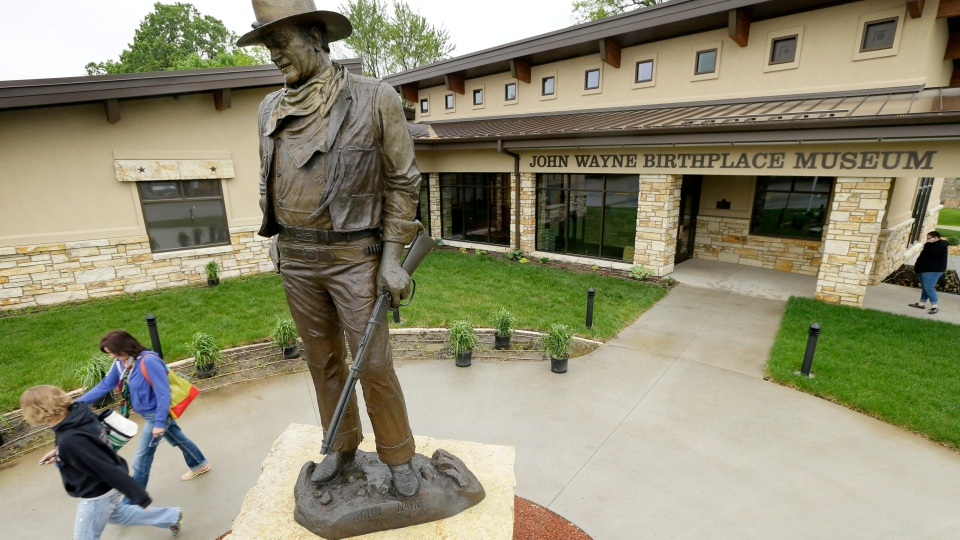 Tourists walk past a statue of John Wayne outside the John Wayne Museum, Thursday, May 14, 2015, in Winterset, Iowa. Though Wayne moved to California at a young age, it's a minor footnote for Winterset, a city of about 5,000 people. On Saturday, May 23, 2015, Winterset will help launch the official opening of the newly built museum celebrating Wayne's life and career. (AP Photo/Charlie Neibergall)