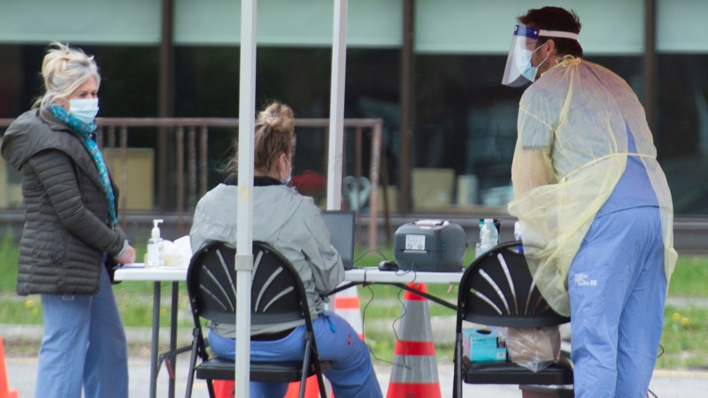 Health-care workers wait for people to tested at a COVID-19 mobile testing clinic in Montreal, Sunday, May 31, 2020, as the COVID-19 pandemic continues in Canada and around the world. THE CANADIAN PRESS/Graham Hughes
