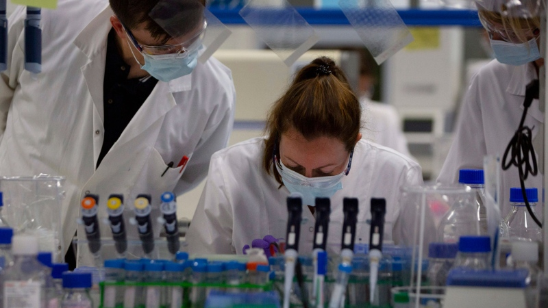 Lab technicians speak with each other during research on coronavirus, COVID-19, at Johnson & Johnson subsidiary Janssen Pharmaceutical in Beerse, Belgium, Wednesday, June 17, 2020. (AP / Virginia Mayo)