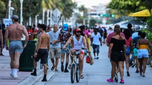 A man rides a bicycle as people walk on Ocean Drive in Miami Beach, Florida on June 26, 2020. (Chandan Khanna/AFP/Getty Images/CNN)
