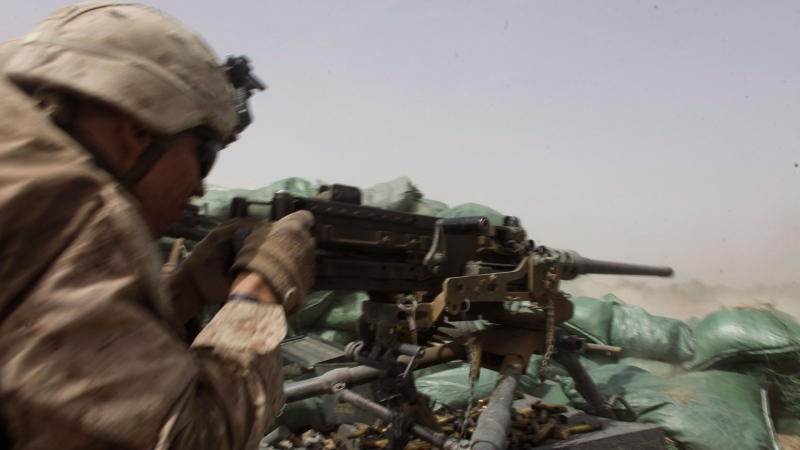 FILE - In this Aug. 25, 2011, file photo, a U.S. Marine fires a heavy machine gun to counter Taliban fire from a nearby tree line in Helmand province, southern Afghanistan.  (Brennan Linsley / AP)
