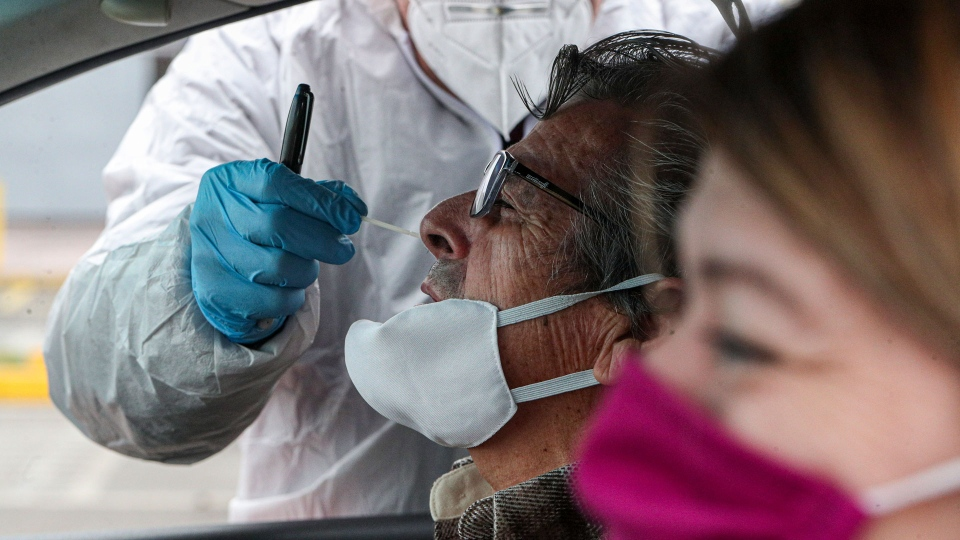 Healthcare worker Patricio Candia takes a nasal swab sample from a man at a new coronavirus testing site, outside a supermarket in Santiago, Chile, Saturday, June 27, 2020.(AP / Esteban Felix)