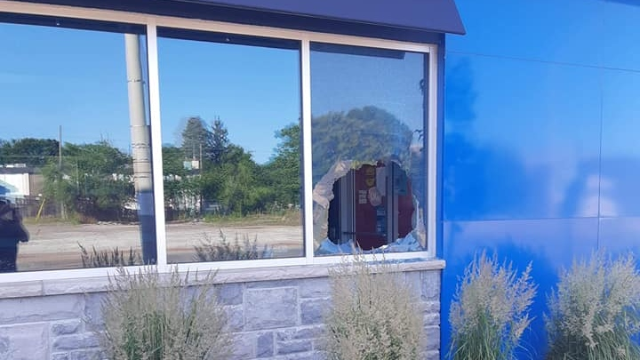 A broken window at a Dairy Queen location in West Brant. Video surveillance from inside shows a person climbing through before making off with a Miracle Network donation bin. (Dairy Queen / Facebook)