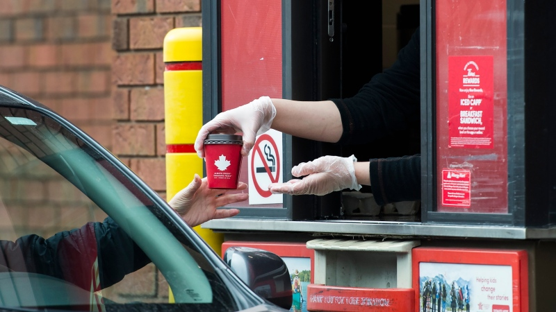 A Tim Hortons employee hands out coffee from a drive-through window to a customer in Mississauga, Ont., on Tuesday, March 17, 2020. THE CANADIAN PRESS/Nathan Denette