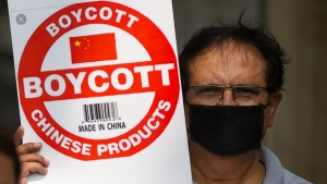 An Indian journalist holds a placard calling for boycott of Chinese products during a protest organized by Working Journalists of India, in New Delhi, India, Tuesday, June 30, 2020. (AP Photo/Altaf Qadri)
