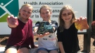 A group of Windsor kids donate proceeds from their painted rocks to the Canadian Mental Health Associationin Windsor, Ont., on June 30, 2020. (Rich Garton / CTV Windsor)