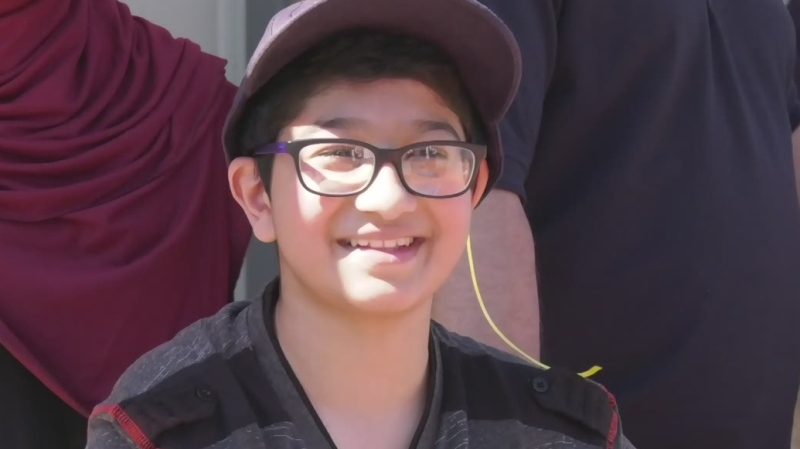 Ahmad Khan, 12, watches the Sunshine Foundation parade at his home in London, Ont. on Tuesday, June 30, 2020. (Marek Sutherland / CTV News)