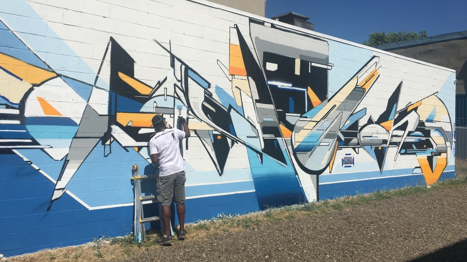 Evond 'Mediah' Blake works on a mural on Talbot Street in St Thomas, Ont. on Tuesday, June 30, 2020. (Brent Lale / CTV News)