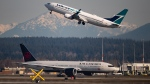 An Air Canada flight departing for Toronto, bottom, taxis to a runway as a Westjet flight bound for Palm Springs takes off at Vancouver International Airport, on March 20, 2020.  (THE CANADIAN PRESS / Darryl Dyck)